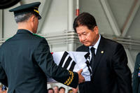 The Republic of Korea (RoK) Vice Minister of Defense Choo Suk Suh, right, bows before the remains of a South Korean service member during the repatriation ceremony at Joint Base Pearl Harbor-Hickam on Sep. 27. (US Marine Corps photo/Jacqueline Clifford)