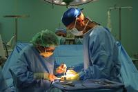 FILE PHOTO – Two doctors perform a procedure on a patient (Image: Health.mil)