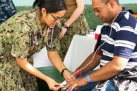 Ensign Kimberly Hill, left, takes the vital signs of a patient during a medical screening provided by the Navy hospital ship USNS Comfort. (US Navy photo/Winterlyn Patterson)