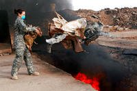 A senior airman tosses unserviceable uniform items into a burn pit at Balad Air Base, Iraq, in March 2008. (US Air Force photo/Julianne Showalter)
