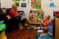 Kathryn Barrager, Child Development Center family child care provider, reads to the children at Joint Base Langley-Eustis, Virginia. (Photo: U.S. Air Force/Senior Airman Derek Seifert)