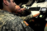 Two servicemembers use tech and a computer.