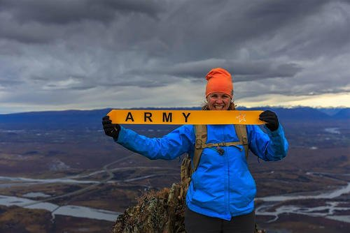 Gold Star sister Maeve Lavtar holds a banner on top of what is now Gold Star Peak near Anchorage, Alaska. (Courtesy of Kirk Alkire)