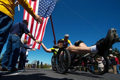 Navy veteran Petty Officer 1st Class Jay Somers gives high fives as he passes through a cheering crowd along the Face of America bike route in Gettysburg, Pa. April 24, 2016. (DoD/EJ Hersom)
