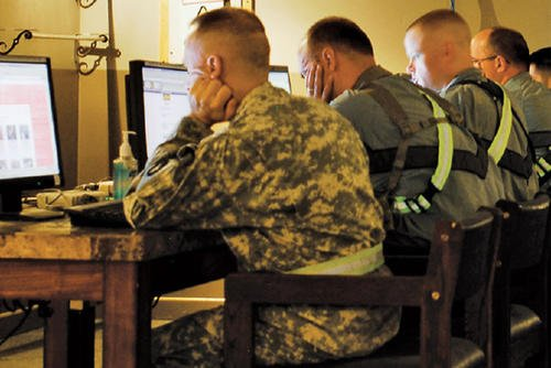 Service members using computers.