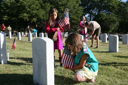 Abrihana Settles, 7, and her sister Sheaten Settles, 9, place flags on graves at the Fort Huachuca Cemetery on Monday morning before the Memorial Day ceremony. Both children are from Girl Scout Troop 9095. (Photo: Natalie Lakosil)